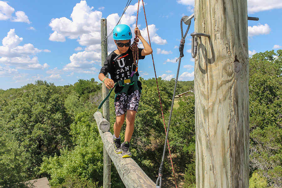 boy walking on the high ropes