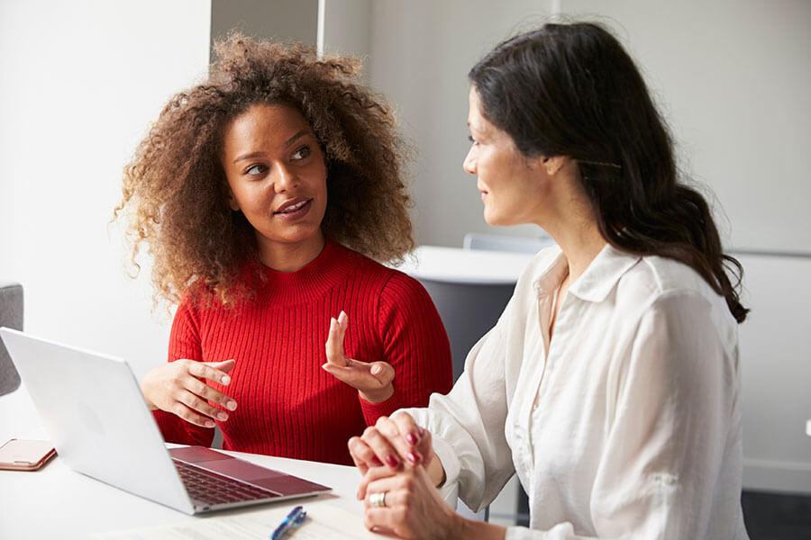 women talking in front of a laptop