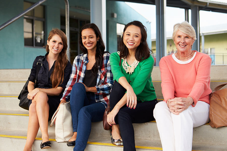 women of various ages smiling