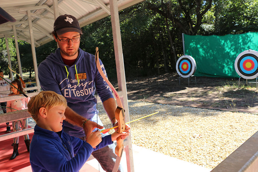 adult teaching archery to child