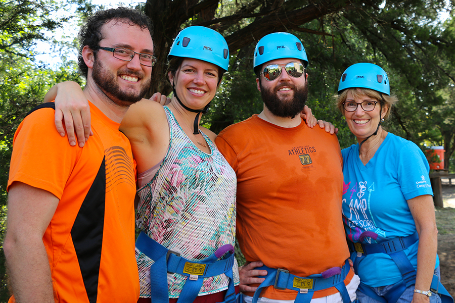 adults wearing helmets and harnesses ready for the challenge course