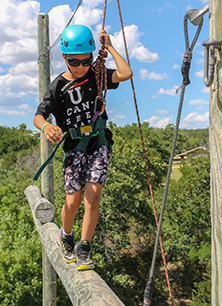 camper on high ropes challenge course catwalk