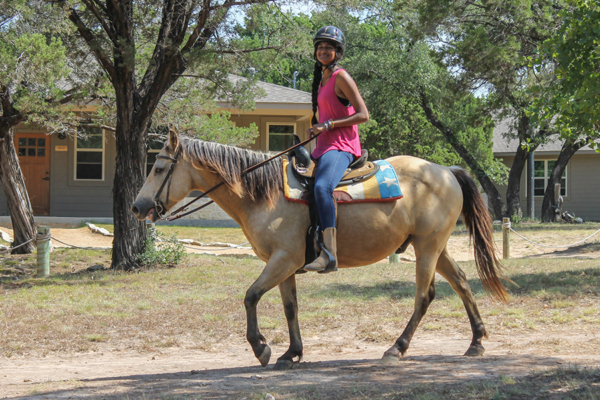 girl camper on horseback smiling