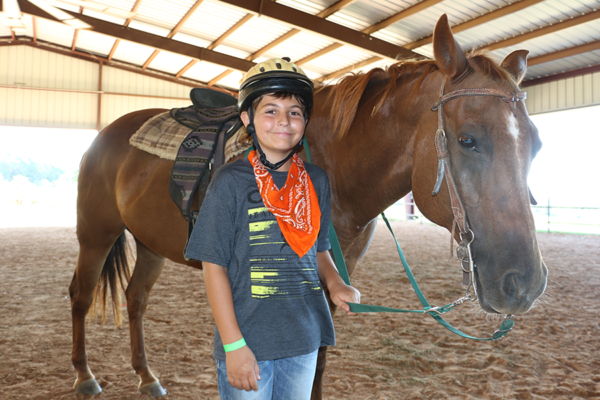 boy camper smiling standing next to horse