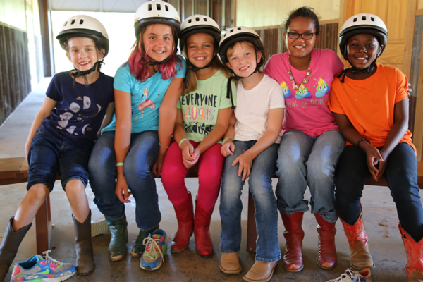 campers in equestrian helmets sitting on bench