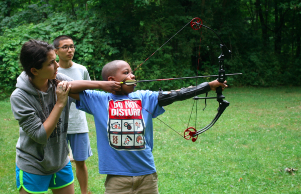 counselor teaching archery to camper